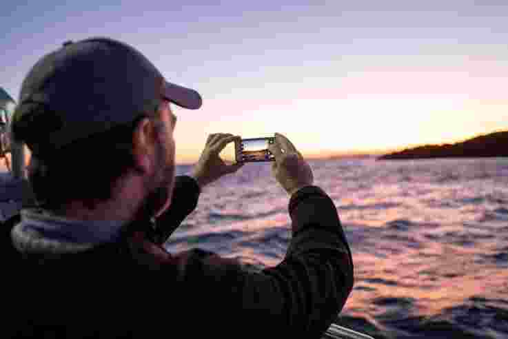 Visitor taking photograph of sunrise while on Catch and Sea Food Tour, Portush